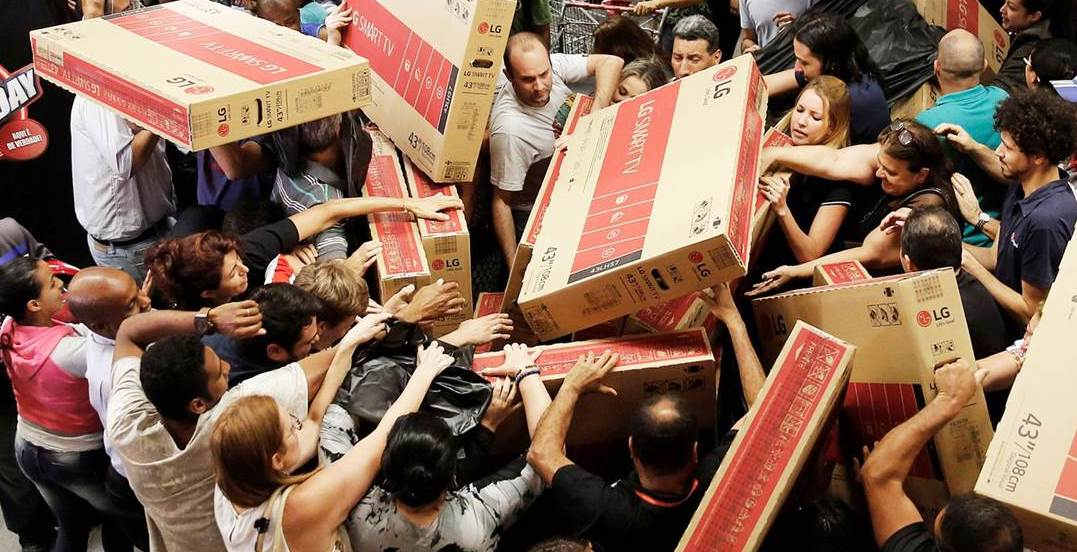 shoppers fight over cardboard boxes, illustrating the psychology of Black Friday in action